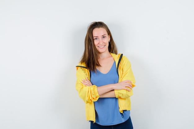 Jonge vrouw in t-shirt, jas staat met gekruiste armen en ziet er zelfverzekerd uit, vooraanzicht.
