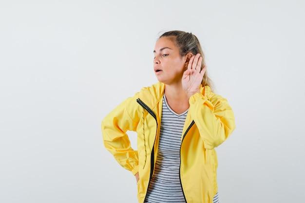 Jonge vrouw in t-shirt, jasje die hand dichtbij oor houdt en nieuwsgierig, vooraanzicht kijkt.
