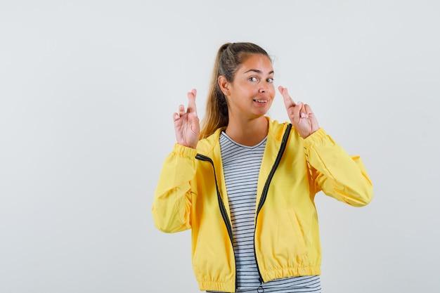 Jonge vrouw in t-shirt, jasje vingers gekruist en op zoek vrolijk, vooraanzicht.