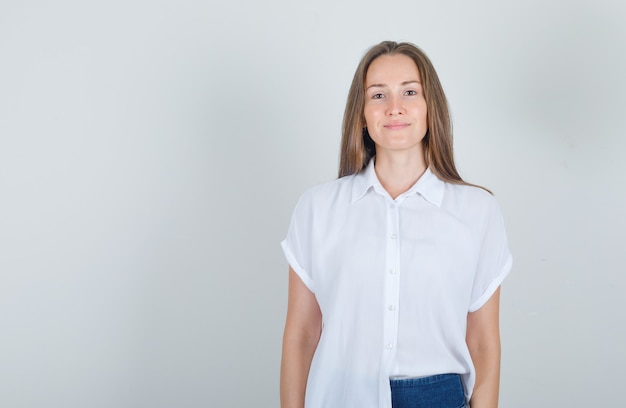 Jonge vrouw in t-shirt, jeans staan en glimlachen