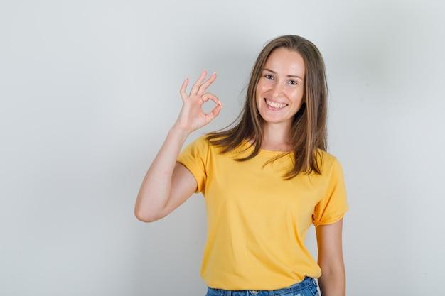 Jonge vrouw in t-shirt, korte broek die en ok teken glimlachen toont