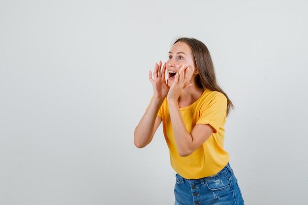 Jonge vrouw in t-shirt, korte broek die iets schreeuwt of aankondigt en er blij uitziet
