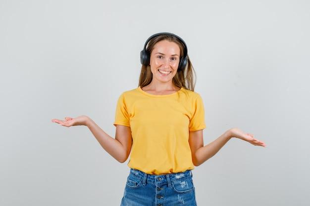 Jonge vrouw in t-shirt, korte broek, hoofdtelefoons die hulpeloos gebaar tonen en blij kijken