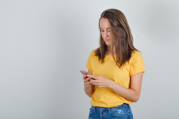 Jonge vrouw in t-shirt, korte broek met behulp van mobiele telefoon en bezig op zoek