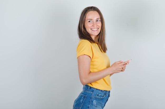 Jonge vrouw in t-shirt, korte broek wegkijken met smartphone in handen en vrolijk kijken.