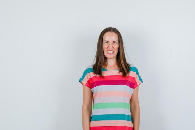 Jonge vrouw in t-shirt lachend met gebalde tanden, vooraanzicht.