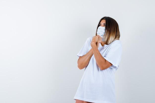 Jonge vrouw in t-shirt, masker met gebalde handen tijdens het kijken en verbaasd kijken, vooraanzicht.