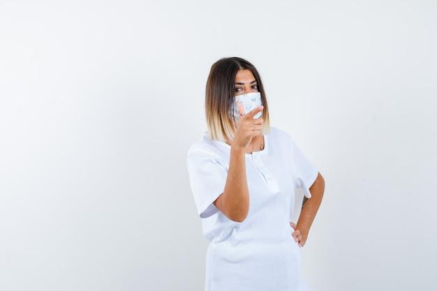 Jonge vrouw in t-shirt, masker opzij wijzend terwijl ze de hand op de taille houdt en er zelfverzekerd uitziet, vooraanzicht.