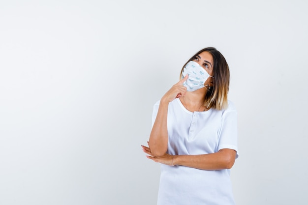 Jonge vrouw in t-shirt, masker staande in denken pose en op zoek doordachte, vooraanzicht.