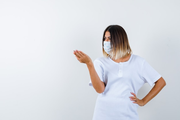 Jonge vrouw in t-shirt, masker strekken hand in vragend gebaar terwijl hand op taille en op zoek ernstig, vooraanzicht.