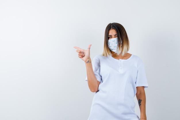 Jonge vrouw in t-shirt, masker wijst naar de linkerkant en kijkt zelfverzekerd, vooraanzicht.