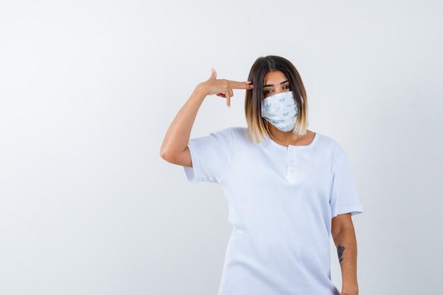 Jonge vrouw in t-shirt, masker zelfmoordgebaar maken en op zoek hopeloos, vooraanzicht.