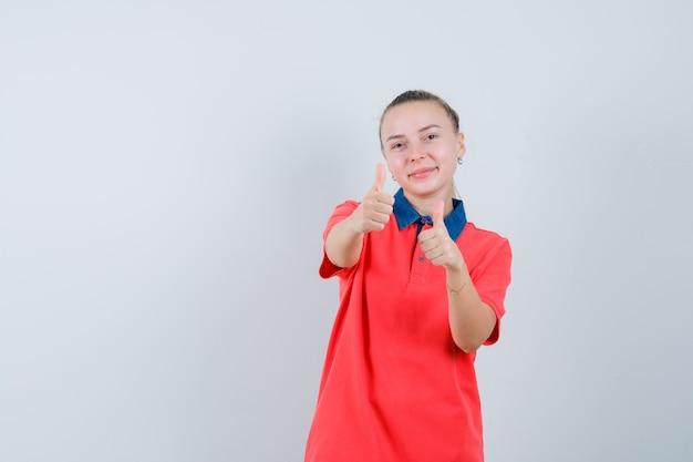 Jonge vrouw in t-shirt met dubbele duimen omhoog en heel kijken