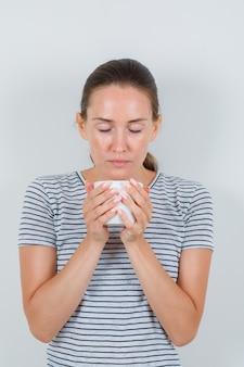 Jonge vrouw in t-shirt met kopje thee met gesloten ogen, vooraanzicht.