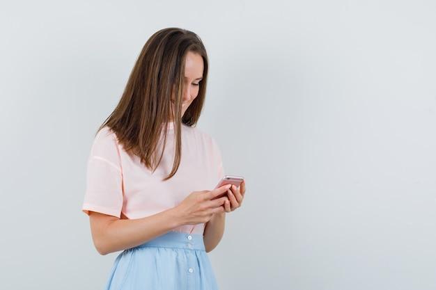 Jonge vrouw in t-shirt, rok met behulp van mobiele telefoon en op zoek gelukkig, vooraanzicht.