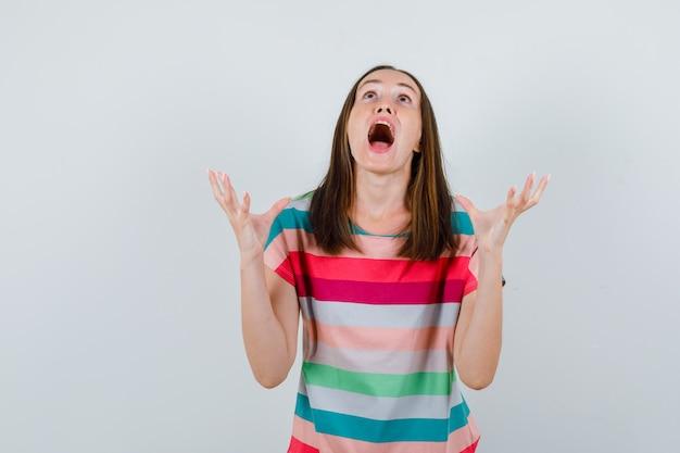 Jonge vrouw in t-shirt schreeuwen en verhogen handen op agressieve manier, vooraanzicht.