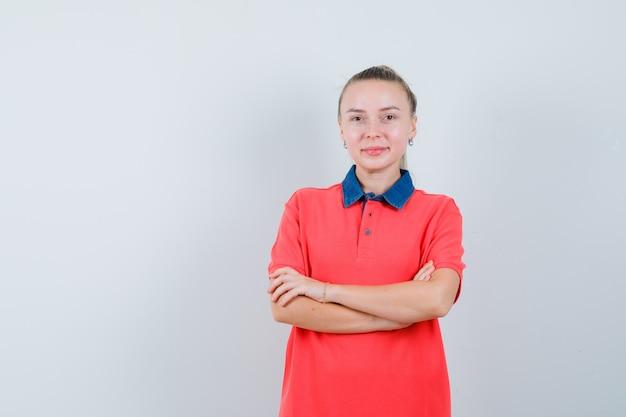 Jonge vrouw in t-shirt staan met gekruiste armen en vrolijk kijken