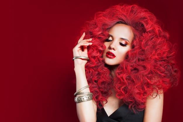 Jonge vrouw in totaal rode stijl. portret van een vrouw met krullend rood haar