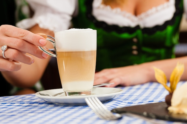Jonge vrouw in traditionele beierse klederdracht in restaurant of pub