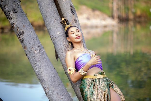Jonge vrouw in traditionele kleding liggen door boomstam