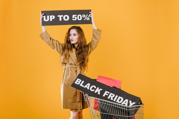 Jonge vrouw in trenchcoat met zwarte vrijdag 50% teken en kleurrijke boodschappentassen in winkelwagen geïsoleerd over geel