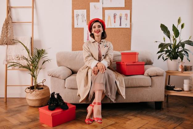 Jonge vrouw in trendy herfst outfit vormt in gezellige kamer. mooie vrouw in modieuze kleding en rode hakken zit op beige bank naast rode dozen.