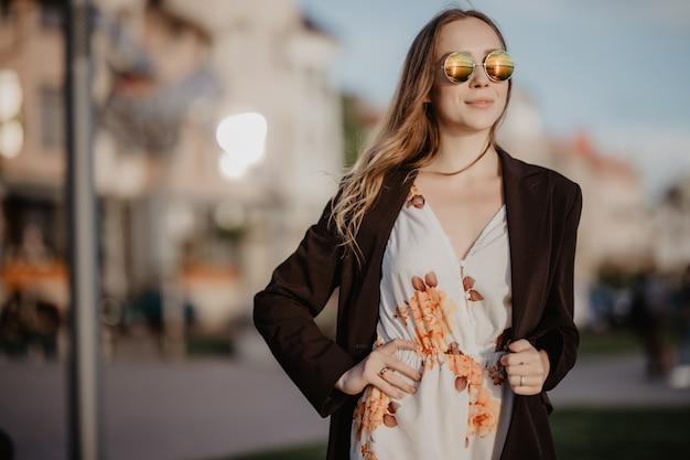 Jonge vrouw in trendy zonnebril en wit poloshirt in een lentedag bij zonsondergang