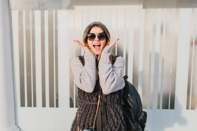 Jonge vrouw in trendy zonnebril genieten van goed weer tijdens ochtendwandeling. openluchtportret van opgewekte vrouw in grijze sweater met zwarte rugzak en poseren met verbaasde gezichtsuitdrukking.