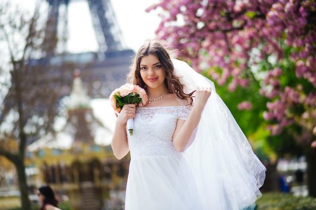 Jonge vrouw in trouwjurk buitenshuis. mooie bruid in een veld bij zonsondergang