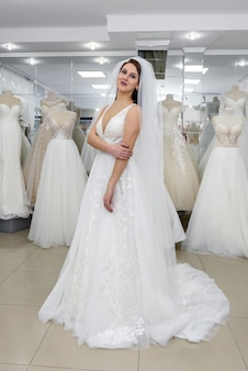Jonge vrouw in trouwjurk en sluier in bruidswinkel