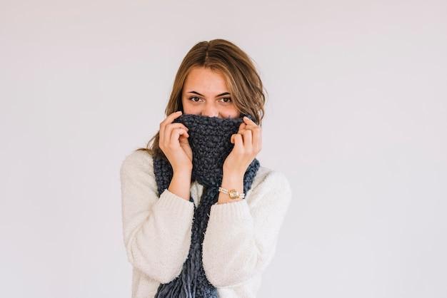 Jonge vrouw in trui en sjaal op gezicht
