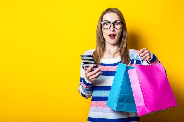 Jonge vrouw in trui houdt boodschappentassen en mobiel