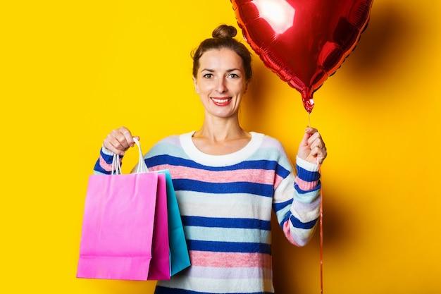 Jonge vrouw in trui met boodschappentassen op gele achtergrond.