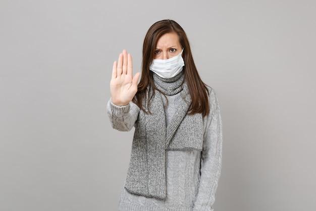 Jonge vrouw in trui, sjaal met steriel gezichtsmasker met stopgebaar met palm geïsoleerd op een grijze achtergrond. gezonde levensstijl, behandeling van zieke ziektes, concept van het koude seizoen. bespotten kopie ruimte.