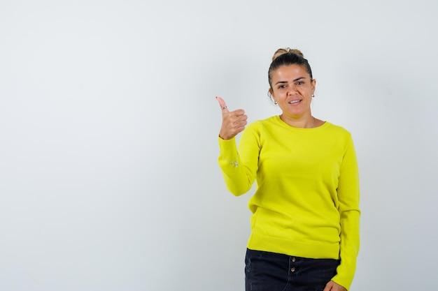 Jonge vrouw in trui, spijkerrok die duim opsteekt en er zelfverzekerd uitziet