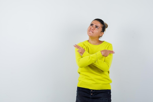 Jonge vrouw in trui, spijkerrok die een pistoolgebaar toont en er hatelijk uitziet