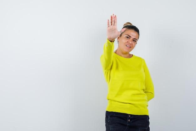 Jonge vrouw in trui, spijkerrok die een stopgebaar toont en er zelfverzekerd uitziet