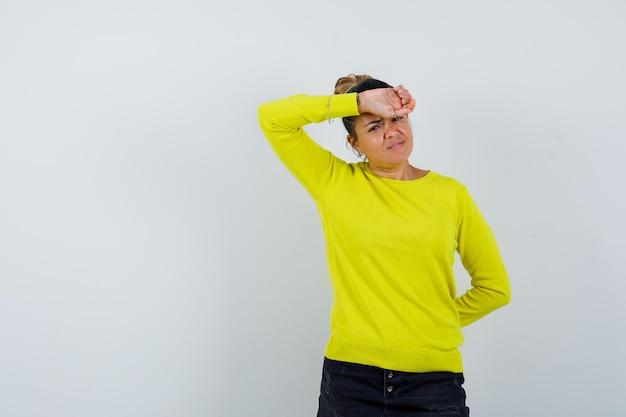 Jonge vrouw in trui, spijkerrok die hand op het voorhoofd houdt en weemoedig kijkt
