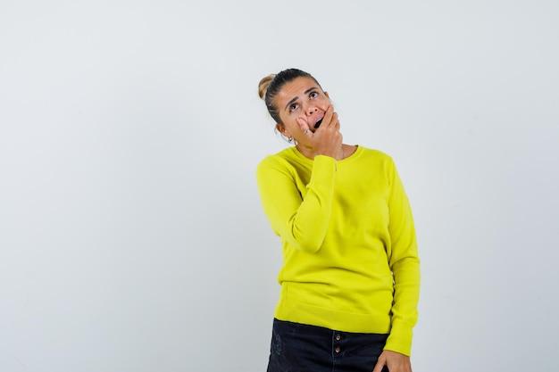Jonge vrouw in trui, spijkerrok die mond bedekt met hand en verbaasd kijkt