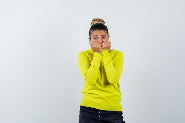 Jonge vrouw in trui, spijkerrok die mond bedekt met vuisten en verbaasd kijkt