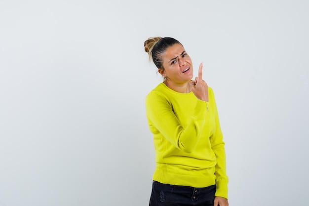 Jonge vrouw in trui, spijkerrok die omhoog wijst en er zelfverzekerd uitziet