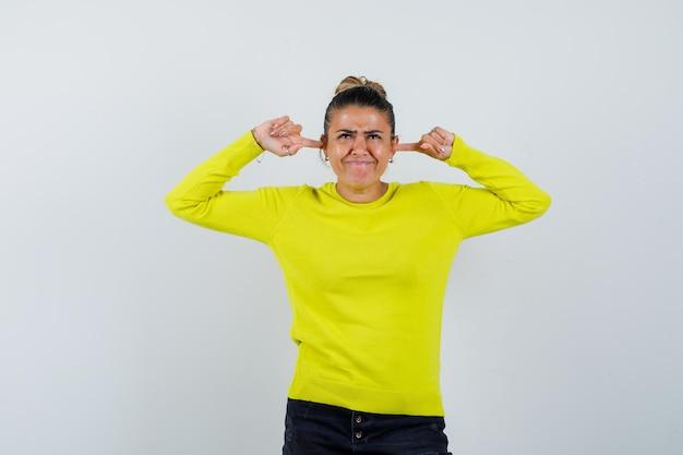 Jonge vrouw in trui, spijkerrok die oren stopt met vingers en er verward uitziet