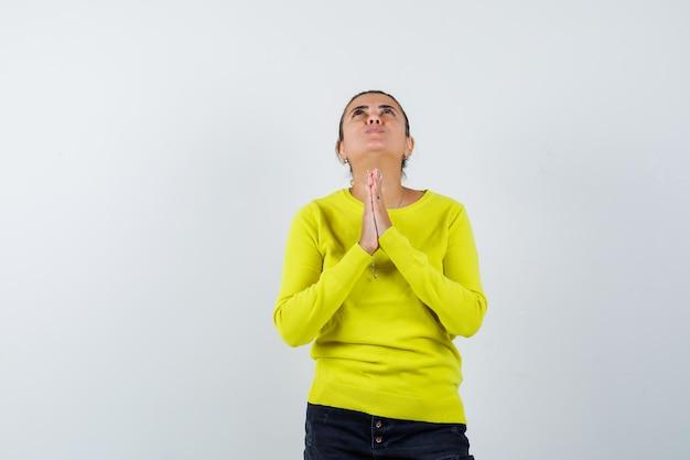 Jonge vrouw in trui, spijkerrok met biddend gebaar en hoopvol kijkend