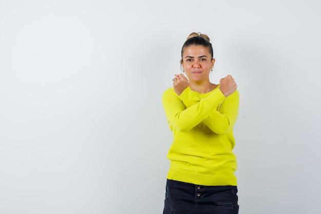 Jonge vrouw in trui, spijkerrok met vuisten gekruist in de buurt van de borst en er zelfverzekerd uit