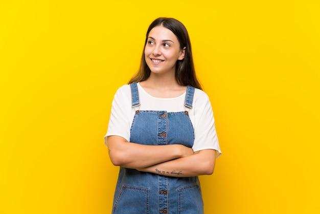 Jonge vrouw in tuinbroek die op geel wordt geïsoleerd dat omhoog terwijl het glimlachen kijkt