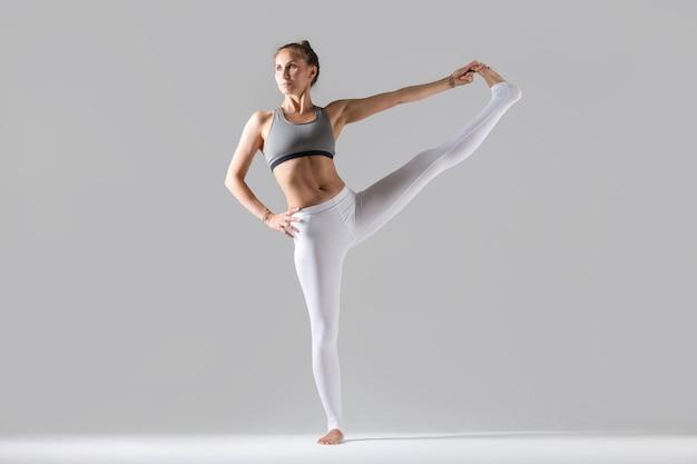 Jonge vrouw in uitgebreide hand naar big toe pose, studio