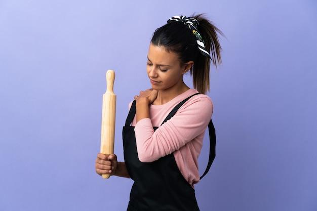 Jonge vrouw in uniform chef-kok die lijdt aan pijn in de schouder omdat ze zich heeft ingespannen
