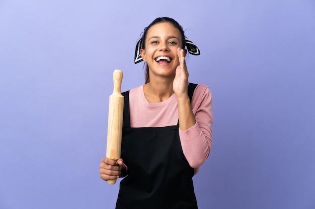 Jonge vrouw in uniform chef-kok schreeuwen met wijd open mond