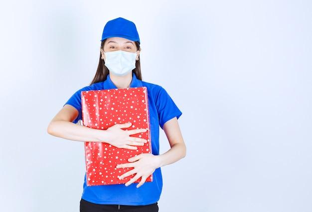 Jonge vrouw in uniform en medisch masker die kerstcadeau knuffelt.