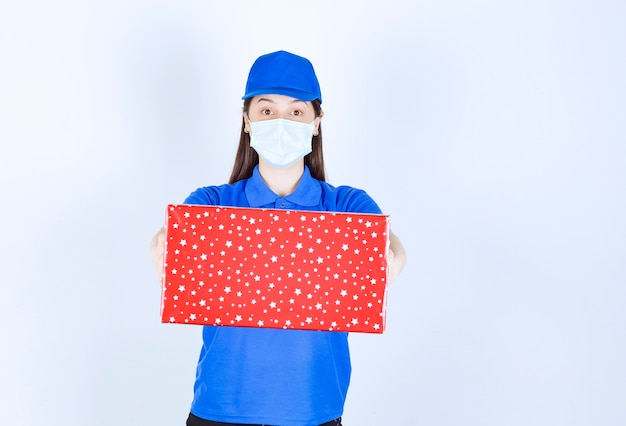 Jonge vrouw in uniform en medisch masker met kerstcadeau.